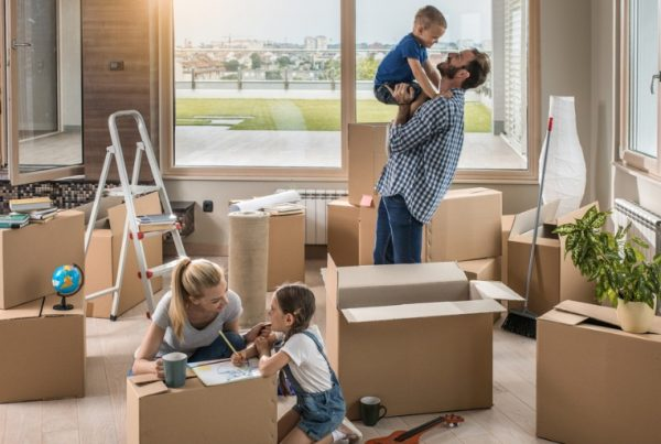 happy-parents-having-fun-with-their-small-kids-in-their-new-apartment-picture-id695847750